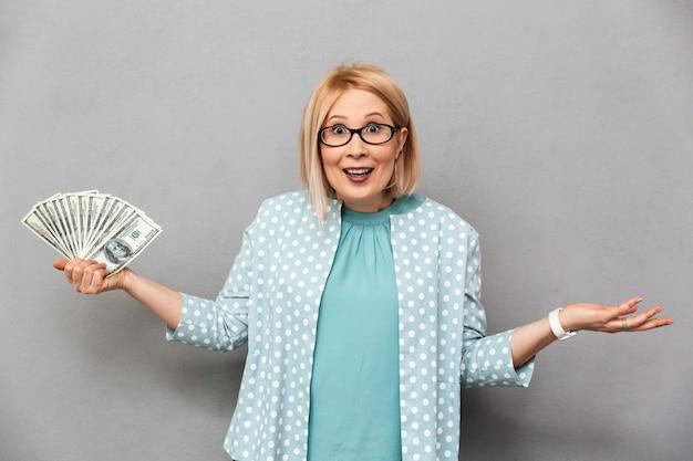 Confondre heureuse femme blonde d'âge moyen en chemisier et lunettes
