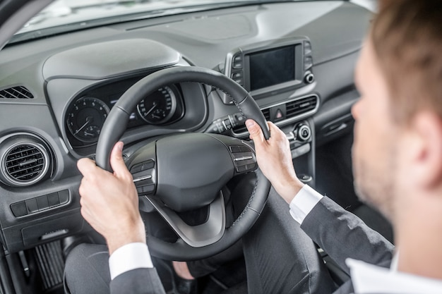 Confort. homme en costume d'affaires assis dans le siège du conducteur tenant le volant d'une nouvelle voiture à l'écoute des sensations de confort