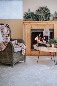 Confortable maison de noël décorée avec une table avec des verres à vin chaud et une chaise avec une couverture