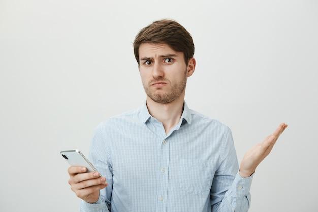 Confus beau mec haussant les épaules, ne peut pas comprendre le message au téléphone
