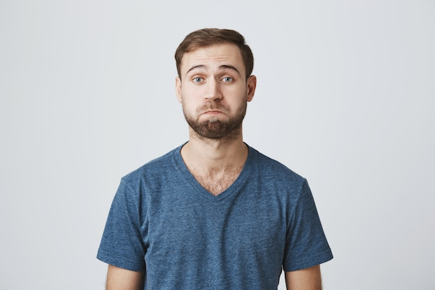 Confus bel homme barbu faisant la moue