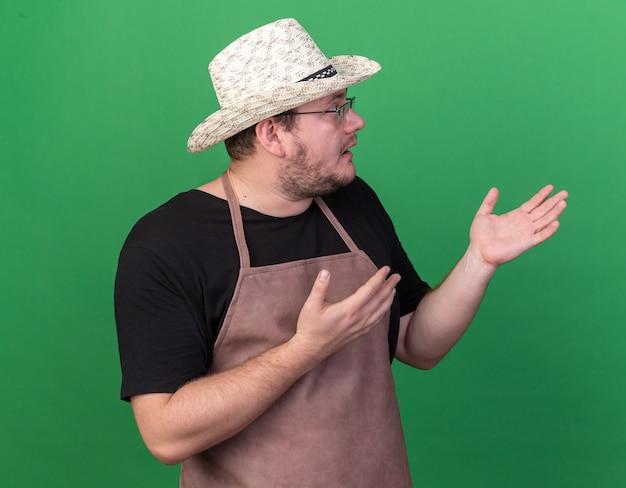 Confus à côté de jeune homme jardinier portant des points de chapeau de jardinage avec les mains sur le côté isolé sur mur vert