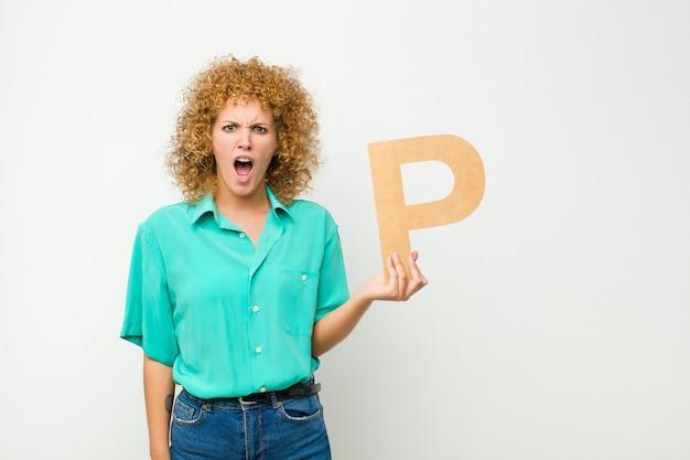 Confus, douteux, pensant, tenant la lettre p de l'alphabet pour former un mot ou une phrase.