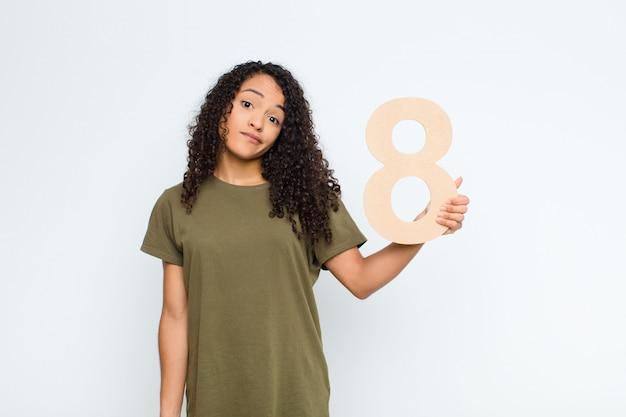 Confus, douteux, pensant, tenant un numéro 8.