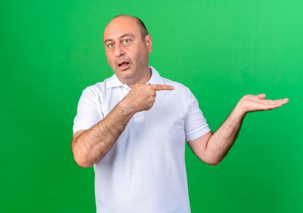 Confus homme mûr occasionnel faisant semblant de tenir et pointe quelque chose