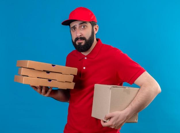 Confus jeune beau livreur de race blanche portant un uniforme rouge et une casquette tenant une boîte en carton et des paquets de pizza isolés sur bleu