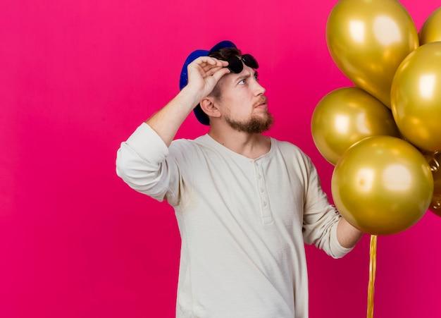 Confus jeune beau mec de fête slave portant chapeau de fête et lunettes de soleil tenant et regardant des ballons tout en tenant des lunettes sur le front isolé sur un mur rose avec espace de copie