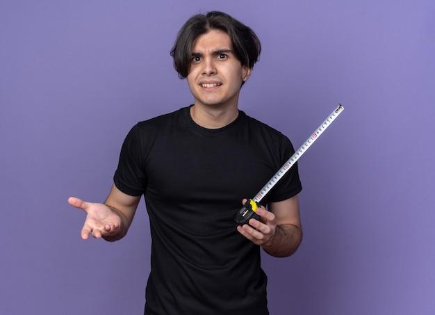 Confus jeune beau mec portant un t-shirt noir qui s'étend sur un ruban à mesurer isolé sur un mur violet