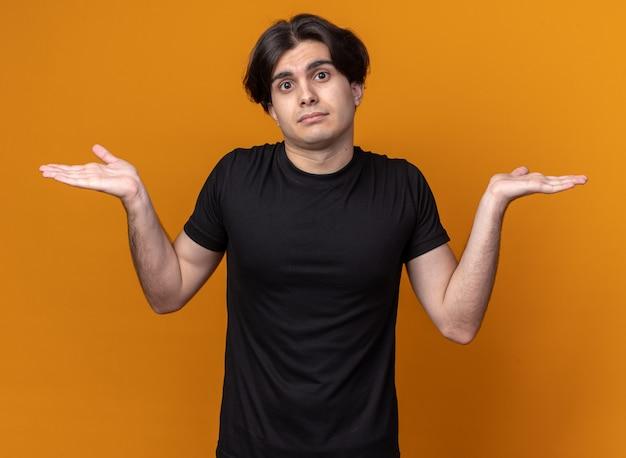 Confus jeune beau mec portant un t-shirt noir répandant les mains isolées sur le mur orange