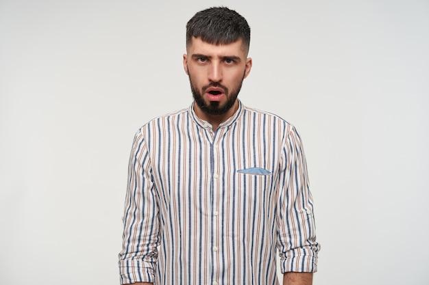 Confus jeune bel homme barbu brune avec une coupe de cheveux courte fronçant les sourcils tout en regardant sérieusement, gardant les mains baissées tout en posant sur un mur blanc