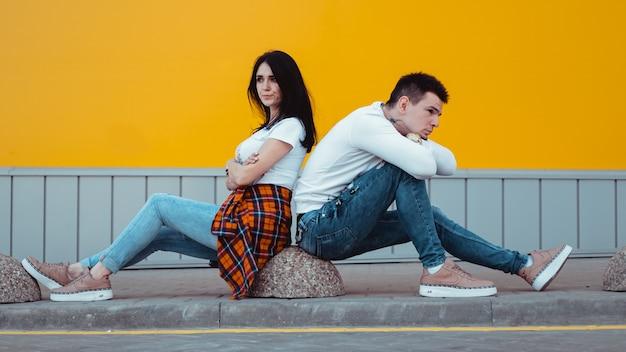 Confus jeune couple debout avec un autre dos avec les bras croisés sur jaune
