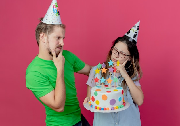 Confus jeune couple portant chapeau de fête se regarde et fille d'anniversaire tient un gâteau isolé sur un mur rose