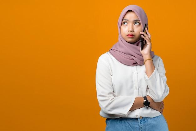 Confus jeune femme asiatique parlant sur smartphone sur jaune