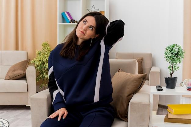 Confus jeune femme assez caucasienne assise sur un fauteuil dans un salon conçu mettant les mains sur la jambe et derrière la tête en regardant à côté