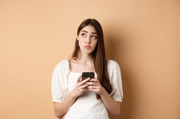 Confus jeune femme pensant après avoir lu les nouvelles sur téléphone mobile, regardant le coin supérieur gauche hésitant, debout sur fond beige.