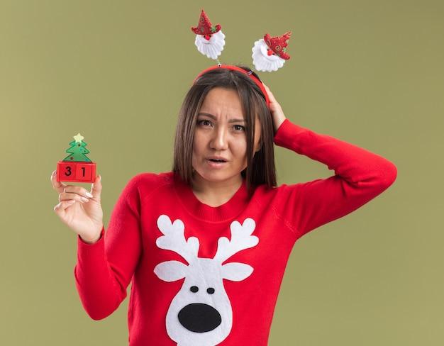 Confus jeune fille asiatique portant le cerceau de cheveux de noël tenant le jouet de noël mettant la main sur la tête isolé sur fond vert olive