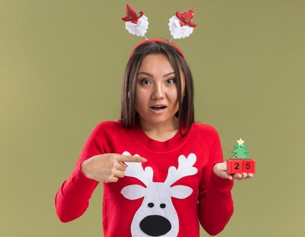 Confus jeune fille asiatique portant cerceau de cheveux de noël tenant et points à jouet de noël isolé sur fond vert olive