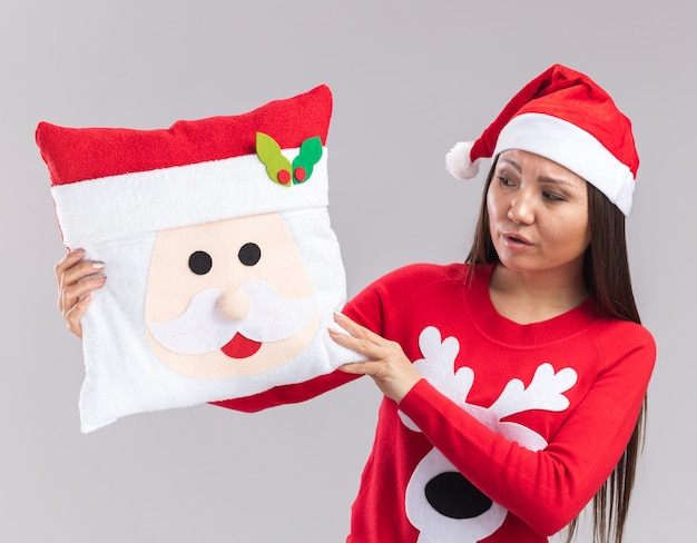Confus jeune fille asiatique portant chapeau de noël avec chandail tenant et regardant oreiller de noël isolé sur fond blanc
