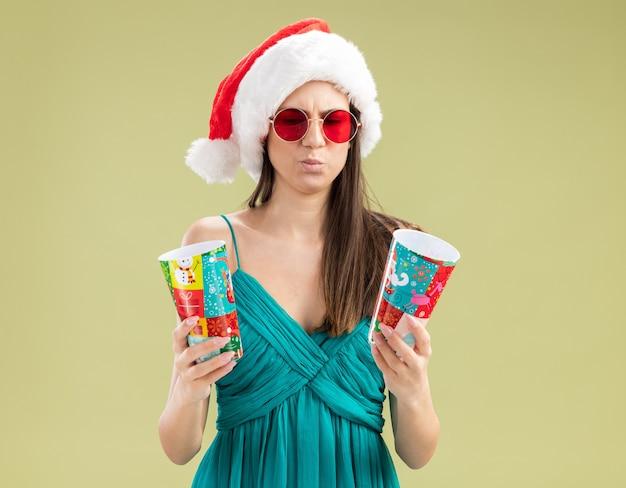 Confus jeune fille caucasienne à lunettes de soleil avec bonnet de noel tenant et regardant des gobelets en papier