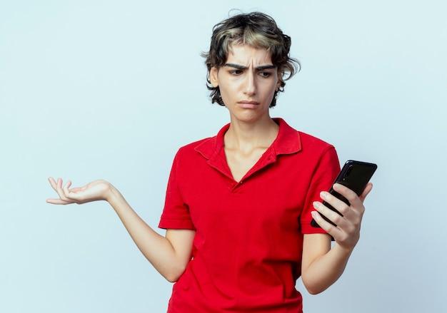 Confus jeune fille de race blanche avec coupe de cheveux de lutin tenant et regardant le téléphone mobile et montrant la main vide isolé sur fond blanc