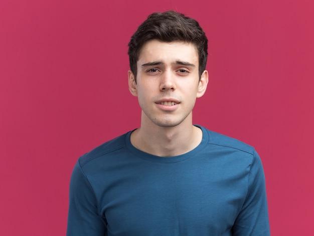 Confus jeune garçon caucasien brune regardant la caméra sur rose