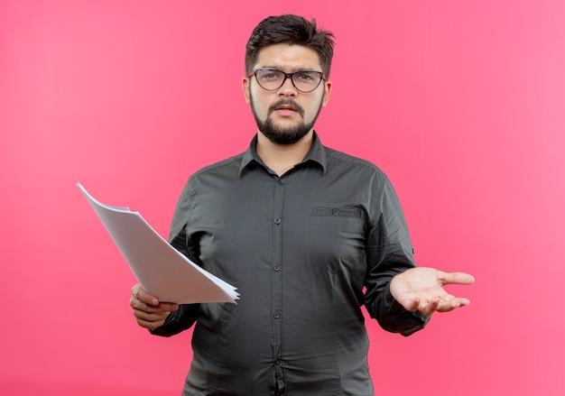Confus jeune homme d'affaires portant des lunettes tenant du papier et répandre la main isolée sur fond rose
