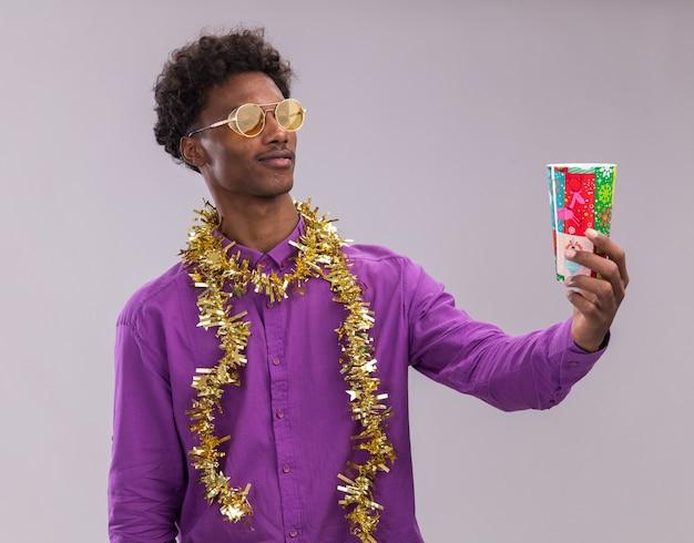 Confus jeune homme afro-américain portant des lunettes avec guirlande de guirlandes autour du cou qui s'étend de la coupe de noël en plastique en le regardant isolé sur fond blanc