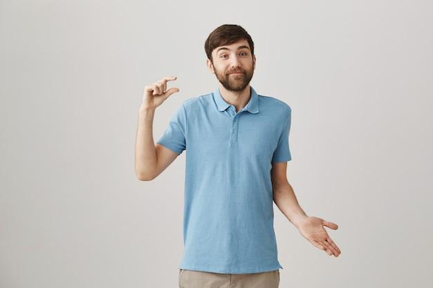 Confus jeune homme barbu posant