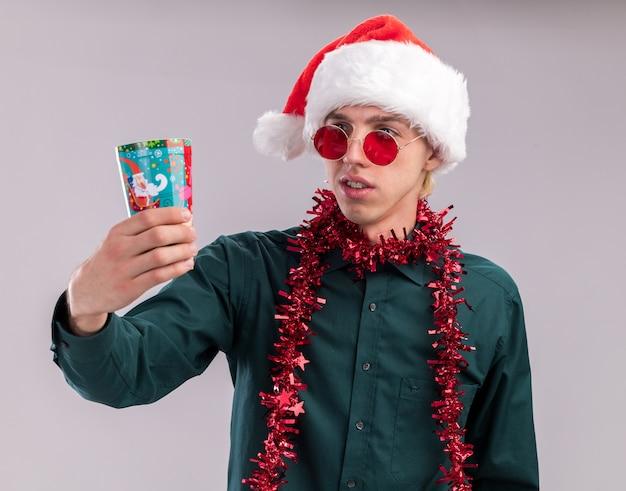 Confus jeune homme blond portant bonnet de noel et lunettes avec guirlande de guirlandes autour du cou qui s'étend de la coupe de noël en plastique en le regardant isolé sur fond blanc