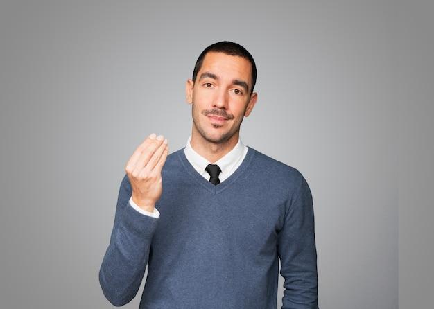 Confus jeune homme faisant un geste italien de ne pas comprendre