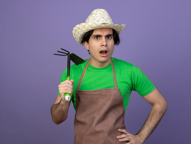 Confus jeune homme jardinier en uniforme portant chapeau de jardinage tenant un râteau houe et mettant la main sur la hanche