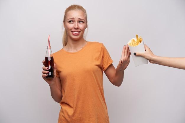 Confus jeune jolie femme blonde avec une coiffure en queue de cheval fronçant les sourcils et levant la main avec un geste de refus tandis que quelqu'un lui offre des frites, isolé sur fond blanc