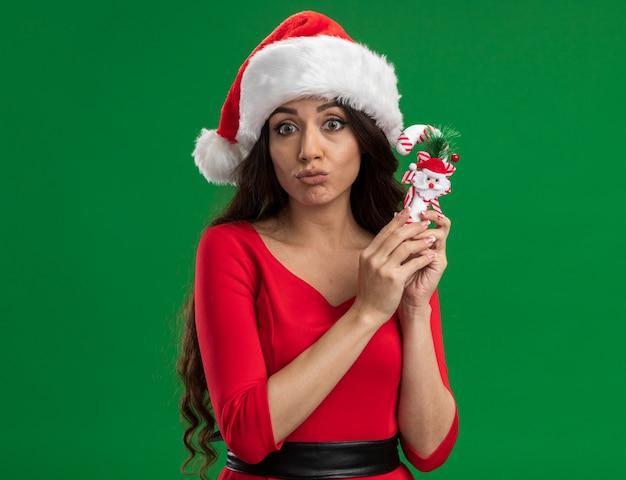 Confus jeune jolie fille portant santa hat holding candy cane ornement regardant la caméra avec les lèvres pincées isolé sur fond vert
