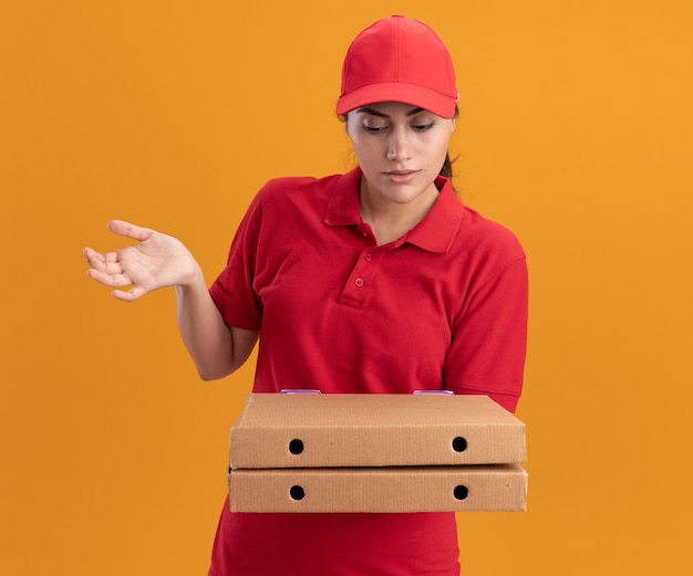 Confus jeune livreuse portant l'uniforme et la casquette tenant et regardant les boîtes de pizza répandre la main isolée sur le mur orange