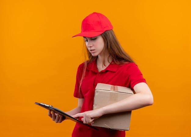 Confus jeune livreuse en uniforme rouge tenant la boîte et en mettant le doigt sur le presse-papiers et en le regardant sur l'espace orange isolé