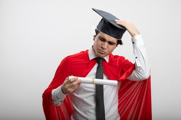 Confus jeune mec super-héros portant cravate et chapeau diplômé tenant et regardant le diplôme mettant la main sur le chapeau isolé sur fond blanc