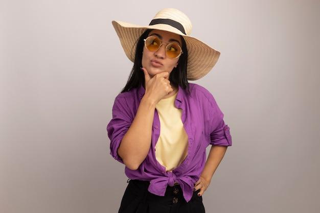 Confus jolie brune fille caucasienne dans des lunettes de soleil avec un chapeau de plage tient le menton et regarde sur le côté sur blanc