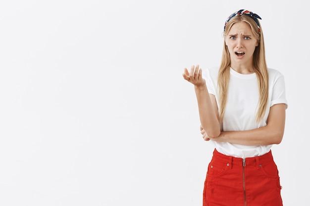 Confus et perplexe jeune fille blonde posant contre le mur blanc