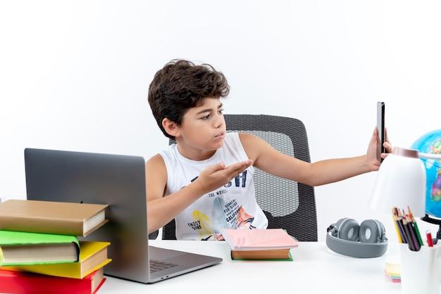 Confus petit écolier assis au bureau avec des outils scolaires tenant et regardant le téléphone