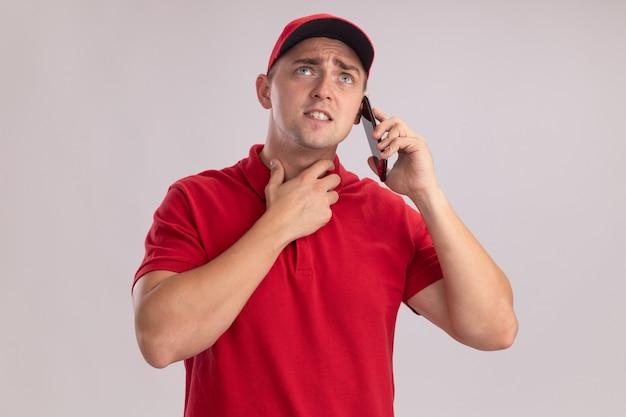 Confus à la recherche d'un jeune livreur en uniforme avec capuchon parle au téléphone isolé sur un mur blanc