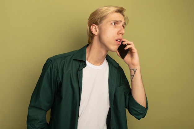 Confus regardant côté jeune mec blond portant un t-shirt vert parle au téléphone