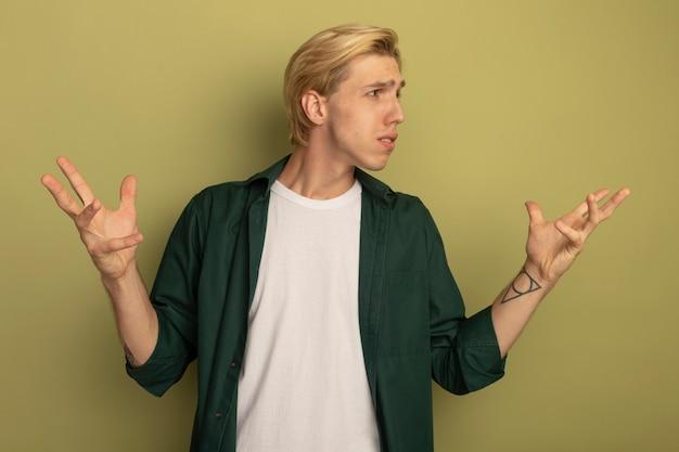 Confus regardant côté jeune mec blond portant un t-shirt vert répandre les mains