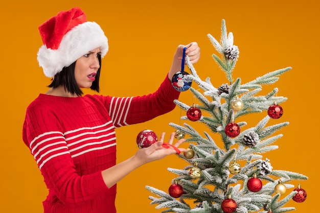 Confus young girl wearing santa hat debout en vue de profil près de sapin de noël décoré tenant et regardant des boules de noël isolé sur mur orange
