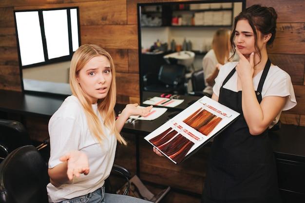 Confuse blonde jeune femme ne peut pas choisir les cheveux de couleur de la palette