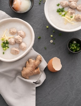 Congee de riz avec du porc haché dans un bol blanc. bol de porridge de riz avec oeuf à la coque. petit déjeuner asiatique