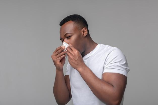 Congestion nasale. homme afro-américain triste en tshirt blanc touchant le mouchoir au nez se sentant malsain
