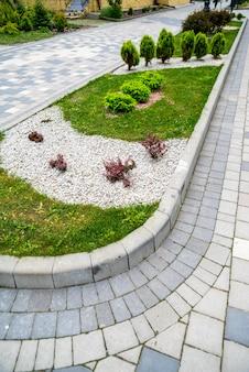 Conifères avec gravier dans la décoration du parterre de fleurs en aménagement paysager