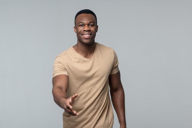 Connaissance, bienvenue. joyeux jeune adulte afro-américain homme étirant sa main avant connaissance accueillant sur fond clair