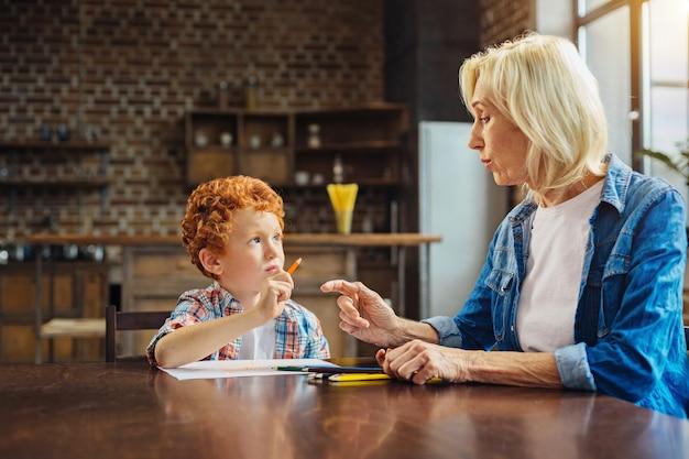 La connaissance est le pouvoir. femme senior consciente de parler à son petit-fils alors que tous les deux étaient assis à une table et se réunissaient à la maison.