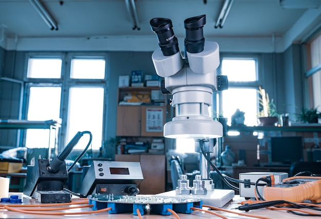 Connecteur coaxial micro-ondes et multimètre numérique électronique sur table d'atelier